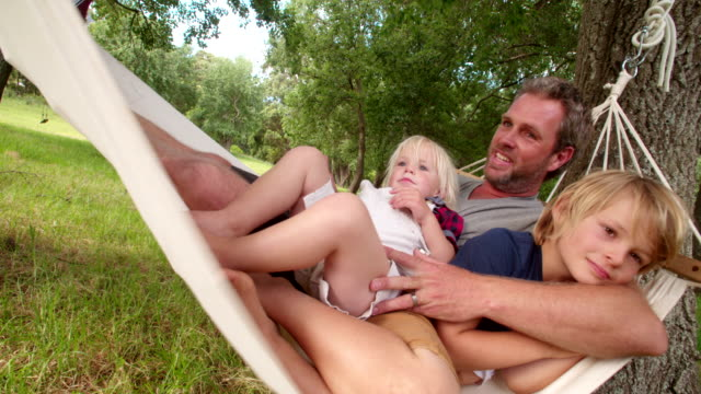 Cheerful dad cuddling his son on a white hammock video