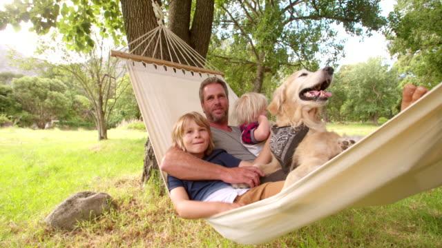 allegro padre abbracciare i suoi due figli in amaca all'aperto - amaca video stock e b–roll
