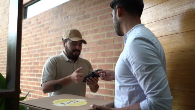 Cheerful delivery man handing pizza order to customer while he pays with credit card
