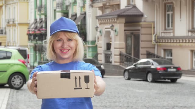 Cheerful delivery woman in blue uniform holding cardboard box Cheerful delivery woman in blue uniform holding cardboard box. Friendly female courier working in delivery service, holding out parcel to the camera. Online consumerism concept post office stock videos & royalty-free footage