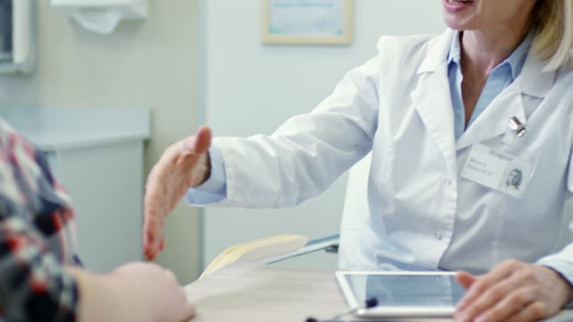 Cheerful Dietician Shaking Hand of Patient Tilt down of cheerful mature female dietician in lab coat talking and shaking hands with overweight patient nutritionist stock videos & royalty-free footage
