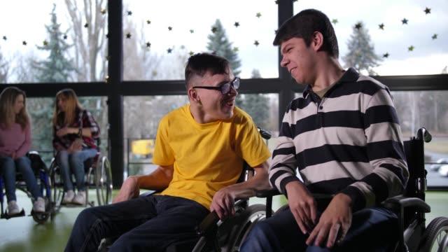 屋内でおしゃべり陽気な障害のある十代の少年たち - disabilitycollection点の映像素材/bロール