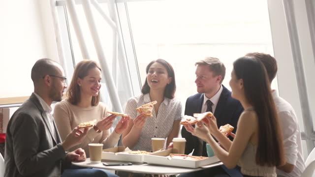 glada olika team människor företag arbetare skrattar äta pizza tillsammans - lunch bildbanksvideor och videomaterial från bakom kulisserna