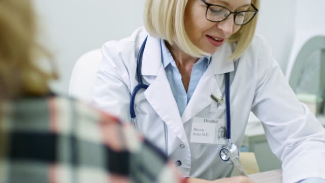 Cheerful Doctor Giving Consultation to Patient Tilt up of cheerful mature doctor in lab coat talking with unrecognizable patient nutritionist stock videos & royalty-free footage