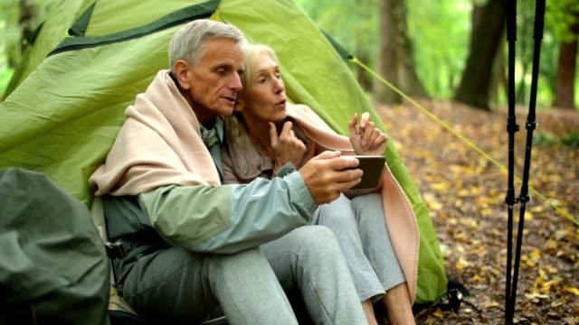 stockvideo's en b-roll-footage met vrolijke bejaarde echtpaar samen rust in de tent - omgeving