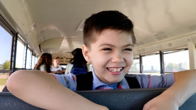 cheerful elementary schoolboy on school bus - school buses stock videos and b-roll footage