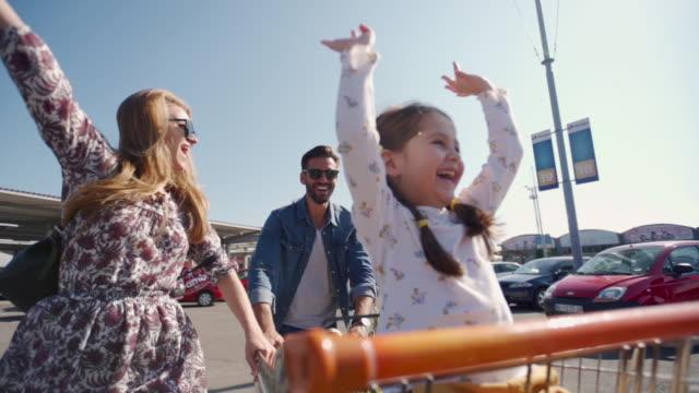 食料品の買い物のためのスーパーマーケットに行く陽気な家族 - 小売り点の映像素材/bロール