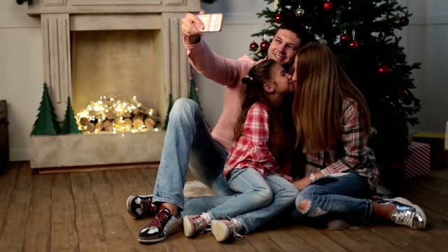 Cheerful family making christmas selfie at home video