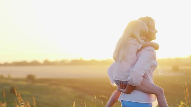en glad familj av två personer som spelar i strålar solen på en grön gräsmatta - sentimentalitet bildbanksvideor och videomaterial från bakom kulisserna