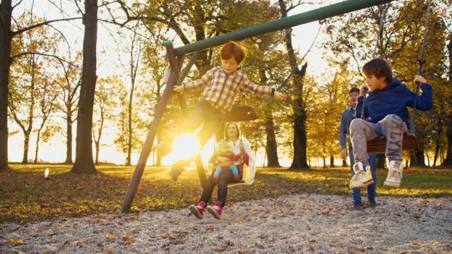 slo, mo, fröhliche familie schwingen im park - kinderspielplatz stock-videos und b-roll-filmmaterial
