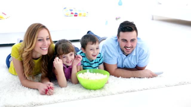 hd: cheerful family watching tv together. - ligga på mage bildbanksvideor och videomaterial från bakom kulisserna