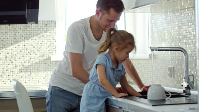陽気な父とお皿を洗う少女 - 援助点の映像素材/bロール