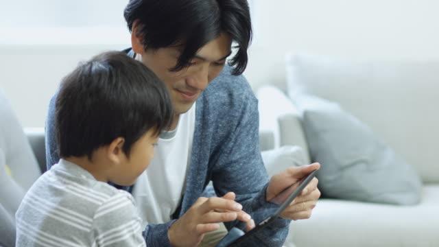 陽気な父と息子のタブレットを一緒に遊んで - 息子点の映像素材/bロール