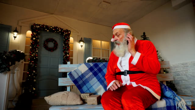 Cheerful Father Christmas congratulating on holiday by smartphone video
