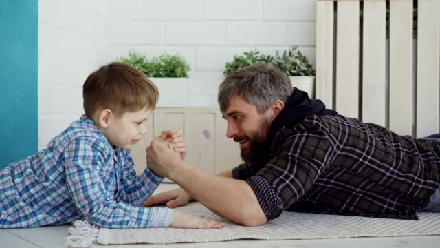cheerful father is teaching his little son arm wrestling, showing him hand position and pretenting to lose, boy is interested and concentrated on new activity. - wrestling stock videos and b-roll footage