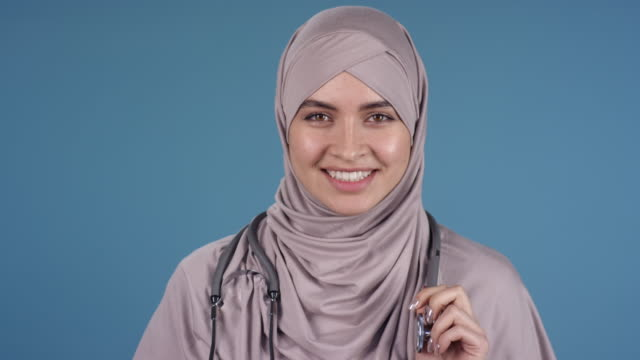 cheerful female doctor in hijab posing - abbigliamento modesto video stock e b–roll