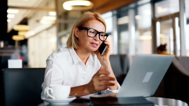 stockvideo's en b-roll-footage met vrolijke vrouwelijke ondernemer spreken op mobiele telefoon en het gebruik van laptop in café - business woman phone