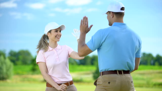Cheerful female golfer with club giving high-five sport coach, teamwork concept