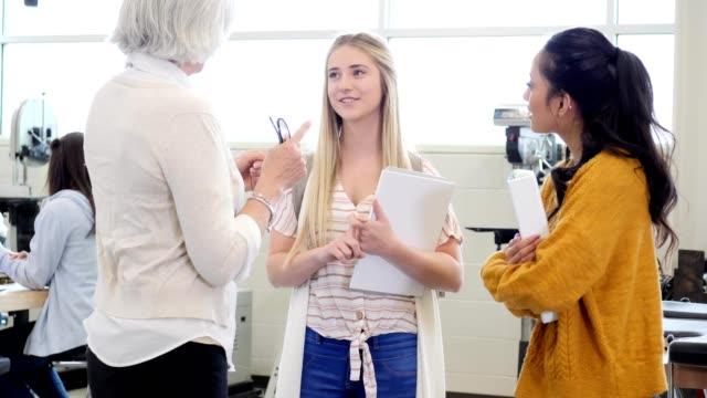 vidéos et rushes de gai femme lycéenne parle avec l'enseignant après la classe - transmission