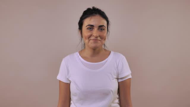 stockvideo's en b-roll-footage met vrolijke vrouw poseren met happy glimlach - wit t shirt