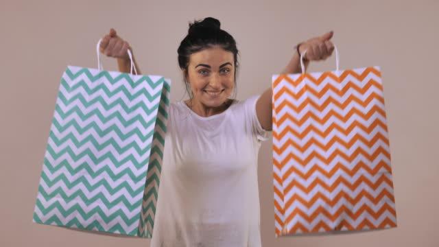 stockvideo's en b-roll-footage met vrolijke vrouw toont boodschappentas - wit t shirt