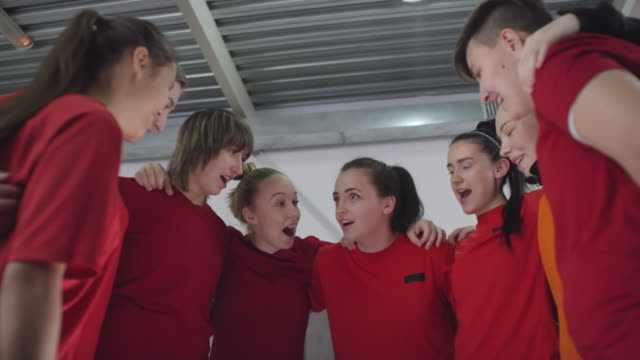 Cheerful Female Soccer Players Huddling in Locker Room