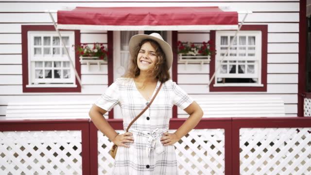 vídeos de stock e filmes b-roll de cheerful female standing near pretty house - aveiro