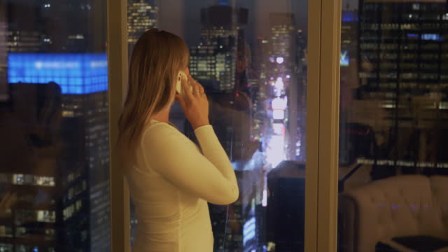 CLOSE UP: Cheerful female tourist talks with her friend over the phone at night