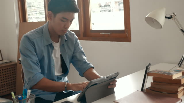 Cheerful freelancer working at home Asian young designer man working with digital tablet at home, Working at home during covid-19, Quarantine at home, Social Distancing casual clothing stock videos & royalty-free footage