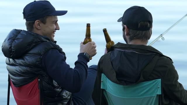 陽気な友達とビールのボトルをチャリンと飲料を飲む時間を釣り - 漁師 外人点の映像素材/bロール