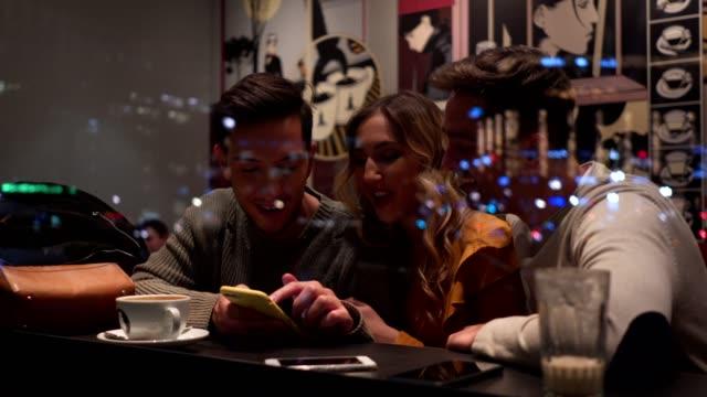 vídeos de stock e filmes b-roll de cheerful friends enjoying coffee at a cafe together - bar local de entretenimento
