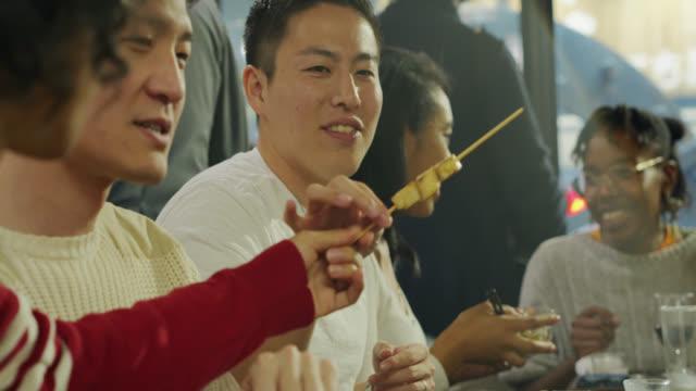 Cheerful Friends Sharing Food at Robabtayaki Restaurant in Tojyo