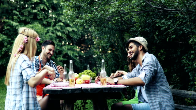 cheerful friends sitting at table and having meal - picnic stock videos and b-roll footage