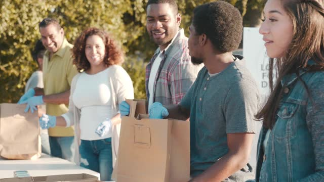 Cheerful friends volunteering together during outdoor food drive A diverse team of people talk with one another as they pack paper bags with food donations. They are working in an assembly line fashion. giving tuesday stock videos & royalty-free footage