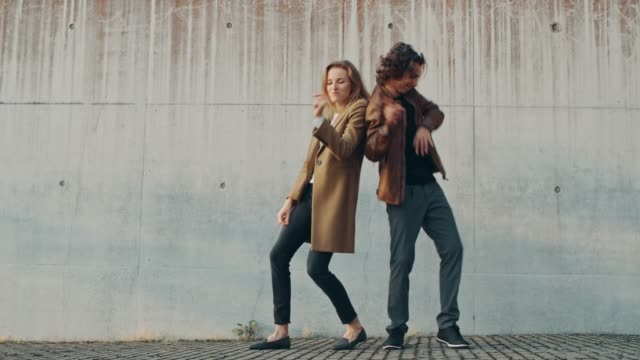 vidéos et rushes de fille joyeuse et jeune homme heureux avec les cheveux longs sont activement danser sur une rue à côté d'un mur de béton urbain. ils portent veste en cuir marron et manteau. jour ensoleillé. - mode femmes