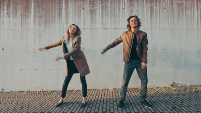 glad flicka och lycklig ung man med långt hår dansar aktivt meme flyttar på en gata bredvid en urban betong vägg. de bär brunt skinn jacka och coat. solig dag. - aktivitet bildbanksvideor och videomaterial från bakom kulisserna