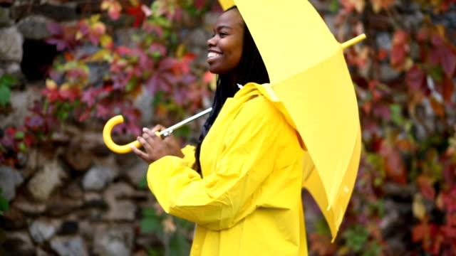 neşeli kız yağmur bekleniyor - sarı stok videoları ve detay görüntü çekimi