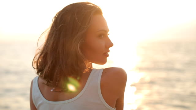 cheerful girl clothed in shorts and a t-shirt posing on the background of golden sunset near the sea - beach fashion stock videos and b-roll footage