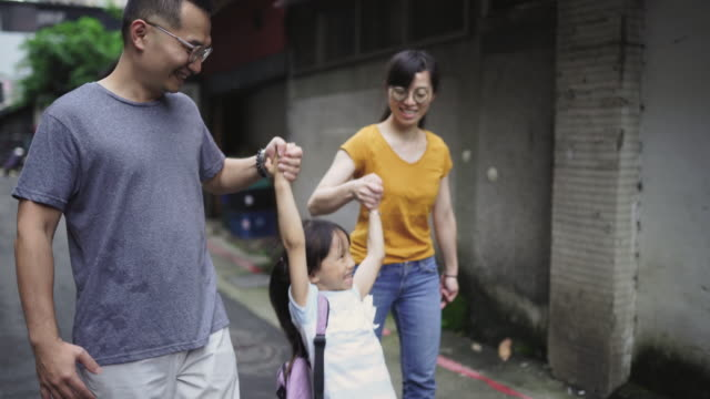 Cheerful girl going to school with mom and dad – film