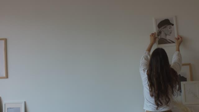 gladlynt flicka hängande bilder på vita väggar inomhus - hänga bildbanksvideor och videomaterial från bakom kulisserna