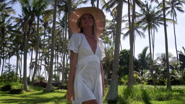 vídeos y material grabado en eventos de stock de chica alegre tener un paseo relajante entre las palmas - disquete