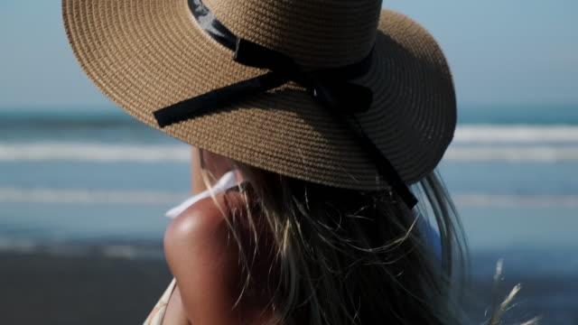 vídeos y material grabado en eventos de stock de chica alegre en bikini y sombrero de sol caminando a lo largo de la costa del océano - disquete