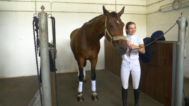 slowmotion: glad flicka i formella slitage tackel upp hennes vackra hingst. - häst tävling bildbanksvideor och videomaterial från bakom kulisserna