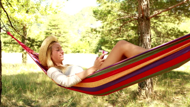Cheerful girl on hammock in summer using digital tablet video