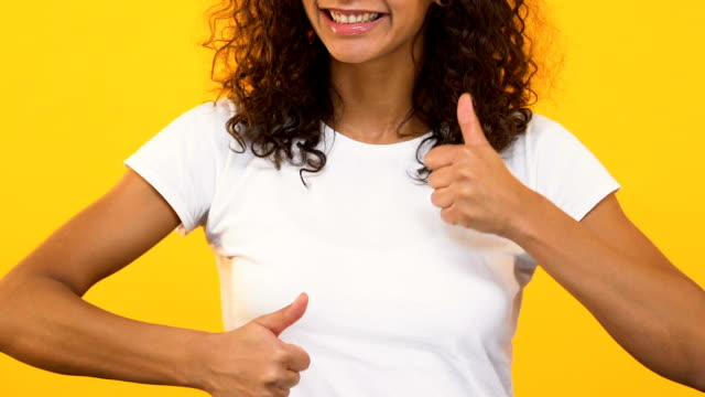 Cheerful girl showing thumbs up, rejoicing success, supporting right choice Cheerful girl showing thumbs up, rejoicing success, supporting right choice representing stock videos & royalty-free footage