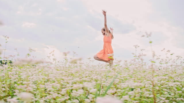 SLO MO Cheerful girl skipping and spinning in the field video
