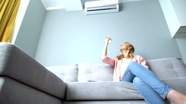 glad tjej slår på luftkonditioneringen, kyla och avfuktning läge - kvinna ventilationssystem bildbanksvideor och videomaterial från bakom kulisserna