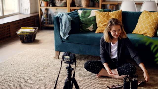 веселая девушка vlogger записывает видео о макияже, косметике и инструментах для своего видеолога с помощью камеры. девушка сидит на полу, пока - элемент здания стоковые видео и кадры b-roll