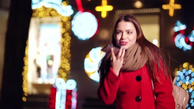 Cheerful girl walking along shops and talking on phone at night video
