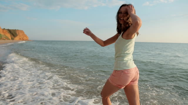 Cheerful girl wearing in the shorts and t-shirt goes barefoot in the water along the beach and smiling video